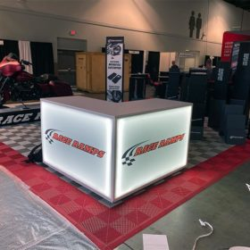 Trade Show Counter Rental Package C3 - LED L-Shaped Reception Counter - Race Ramps - LV Exhibit Rentals in Las Vegas